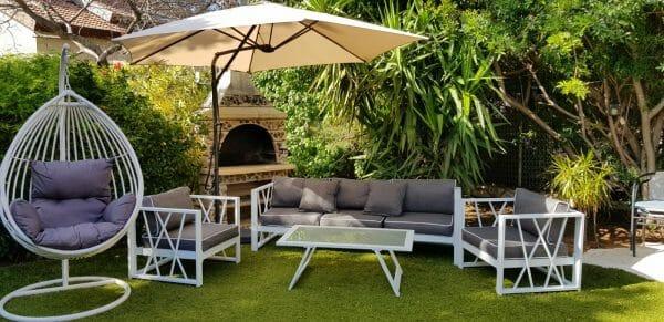 מערכת ישיבה לגינה שולחן כסאות וספה בגווני אפור וערסל נדנדה תלוי